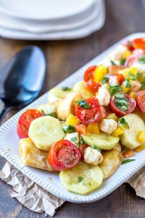 Panzanella on a rectangular tray next to a black spoon