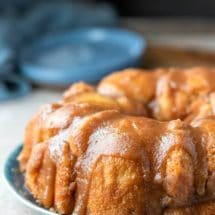 Platter of monkey bread on a blue plate next to two blue plates