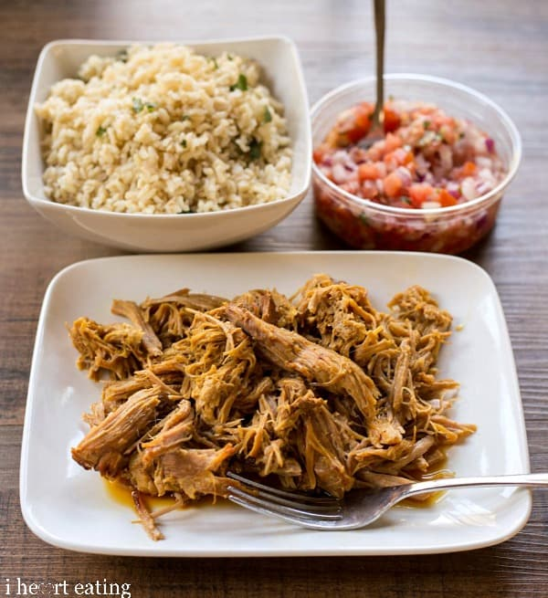 Slow Cooker Cuban Pork on a white plate next to rice and pico de gallo.