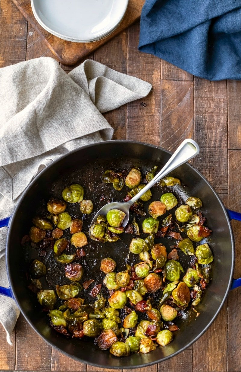 Maple bacon balsamic brussels sprouts in a cast iron pan with a silver spoon