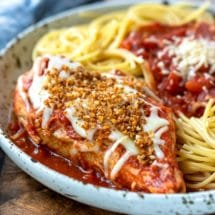 Slow cooker chicken parmesan on a speckled plate