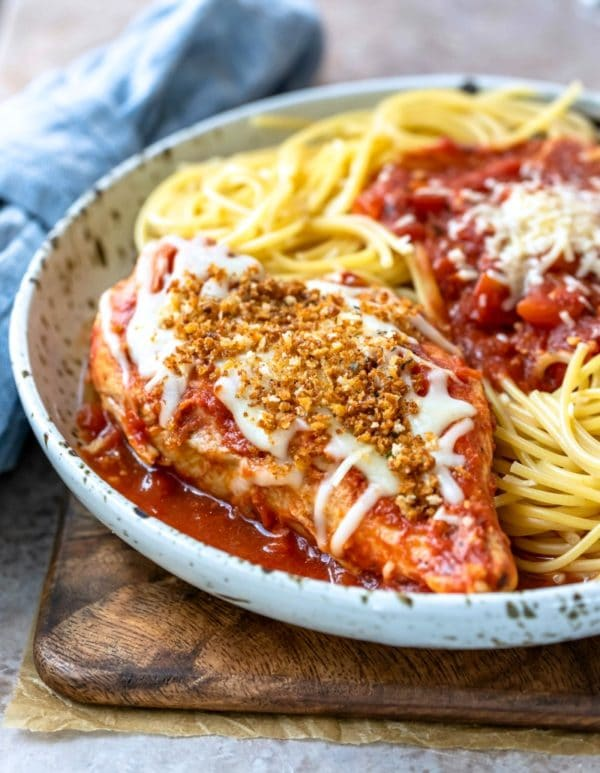 Chicken parmesan and spaghetti on a speckled plate