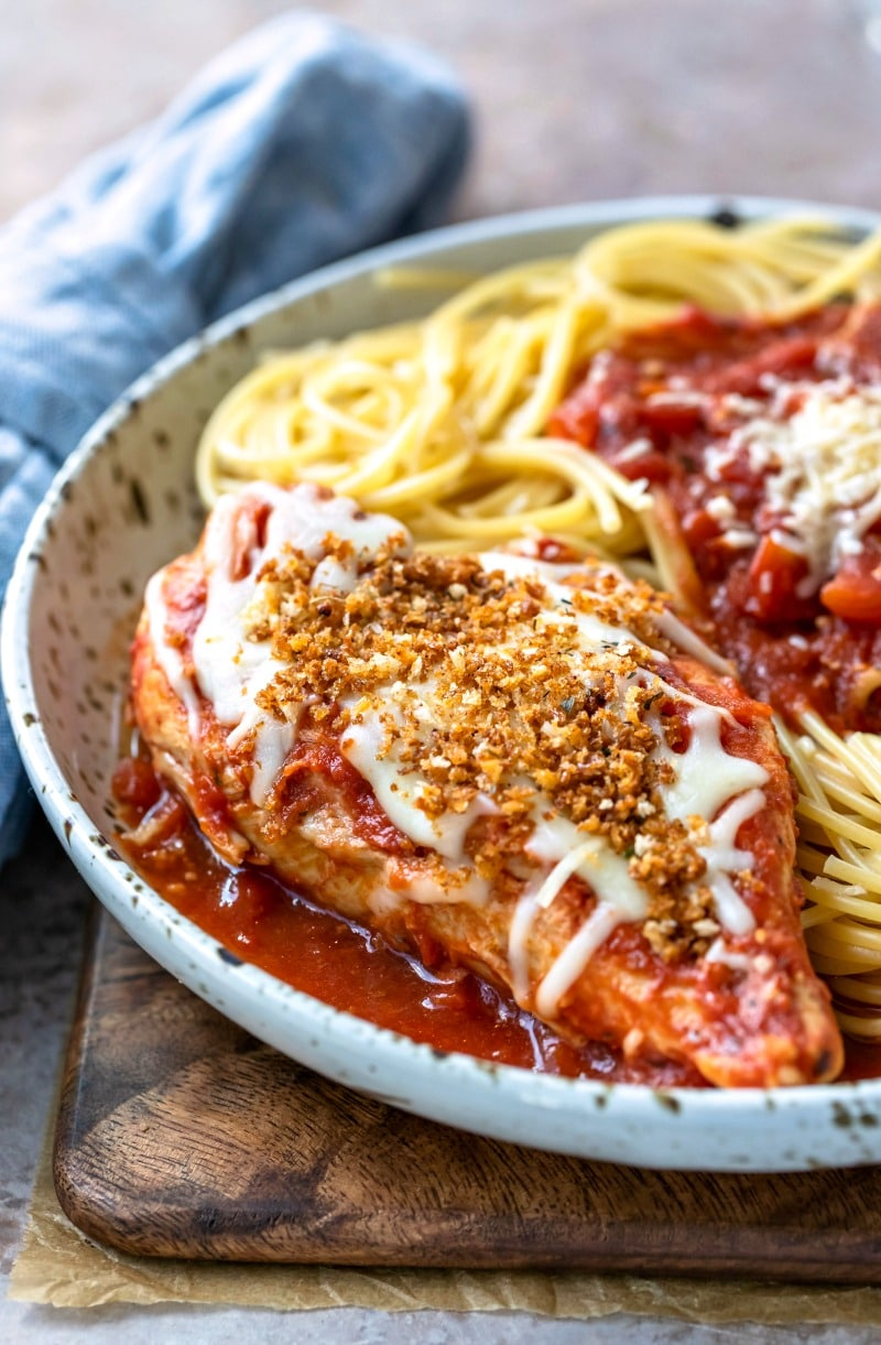Plate with crock pot chicken parmesan topped with cheese and bread crumbs