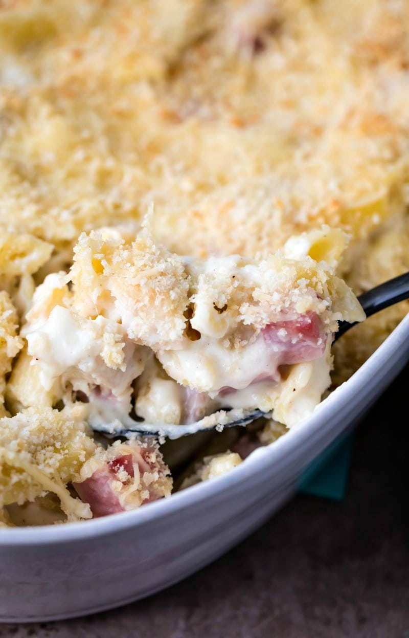 Scoop of chicken cordon bleu casserole coming out of a white baking dish