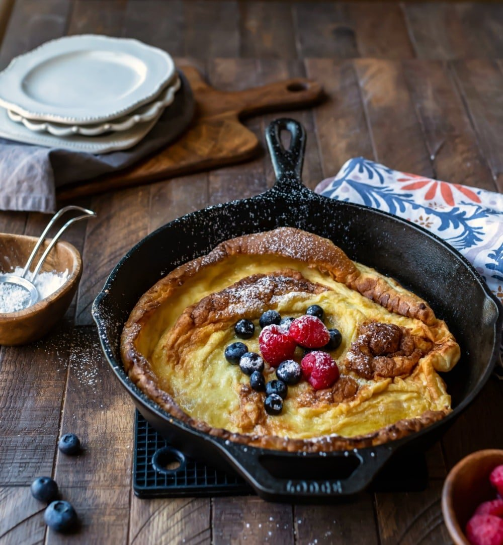 Dutch Baby Pancake in a cast iron skillet dusted with powdered sugar