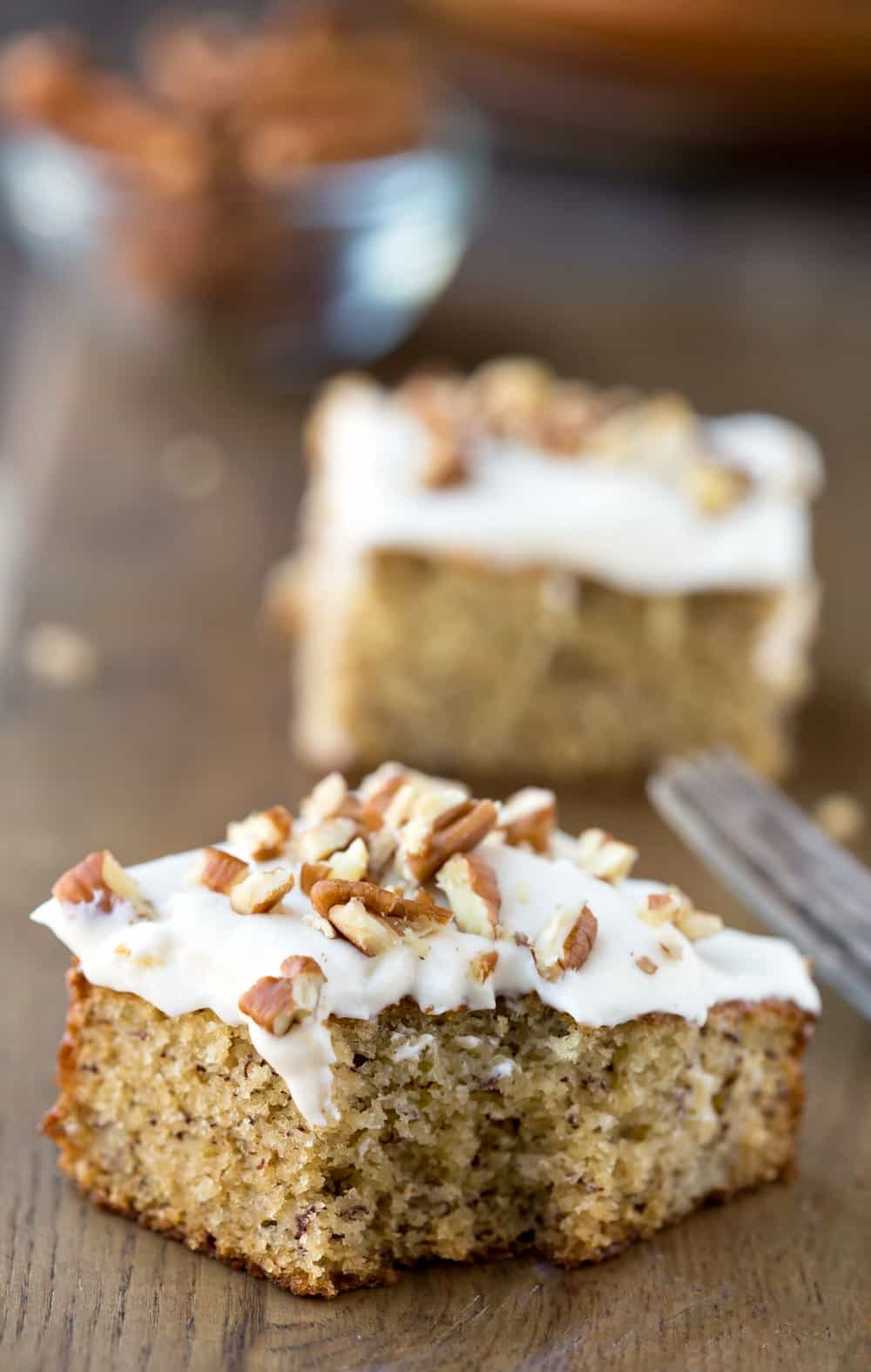 Banana Cake with Cream Cheese Frosting on a wooden background