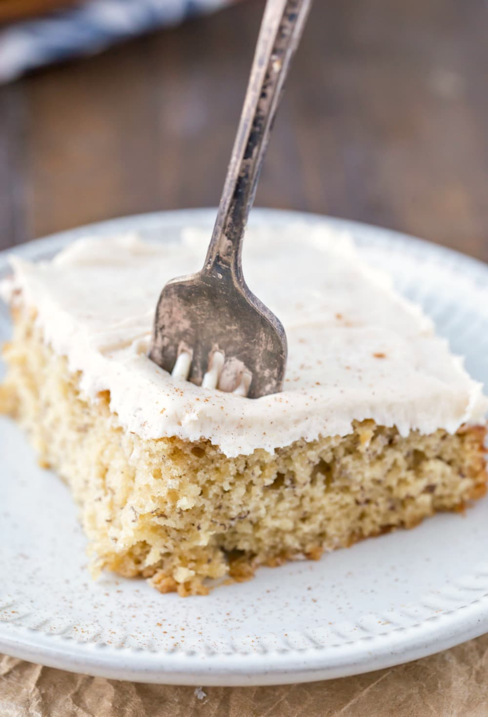 Banana Cake with Cream Cheese Frosting on a white plate with a silver fork