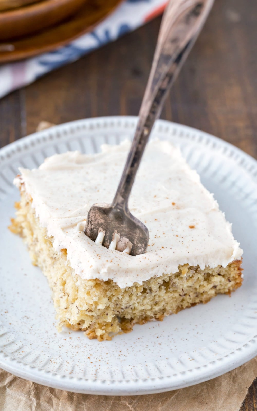 Overhead picture of banana cake with cream cheese frosting with a silver fork in it