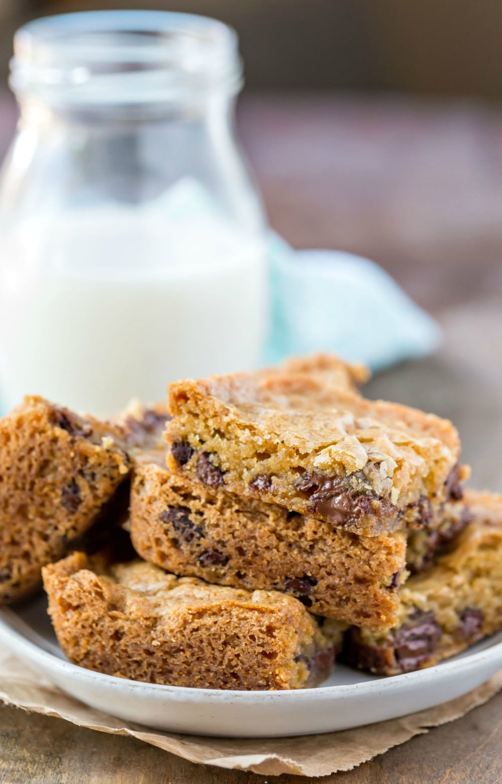 Stack of chewy chocolate chip cookie bars on a white plate next to a glass of milk