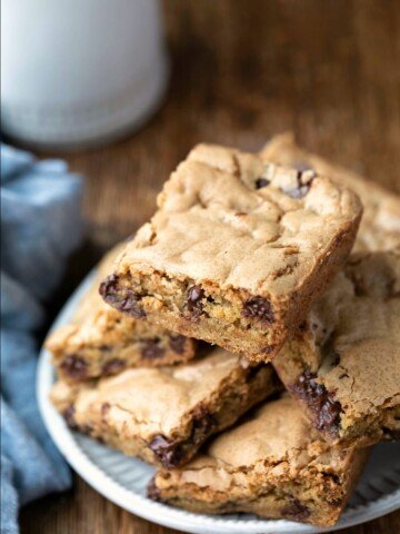 Stack of Chewy Chocolate Chip Cookie Bars on a plate next to a glass of milk