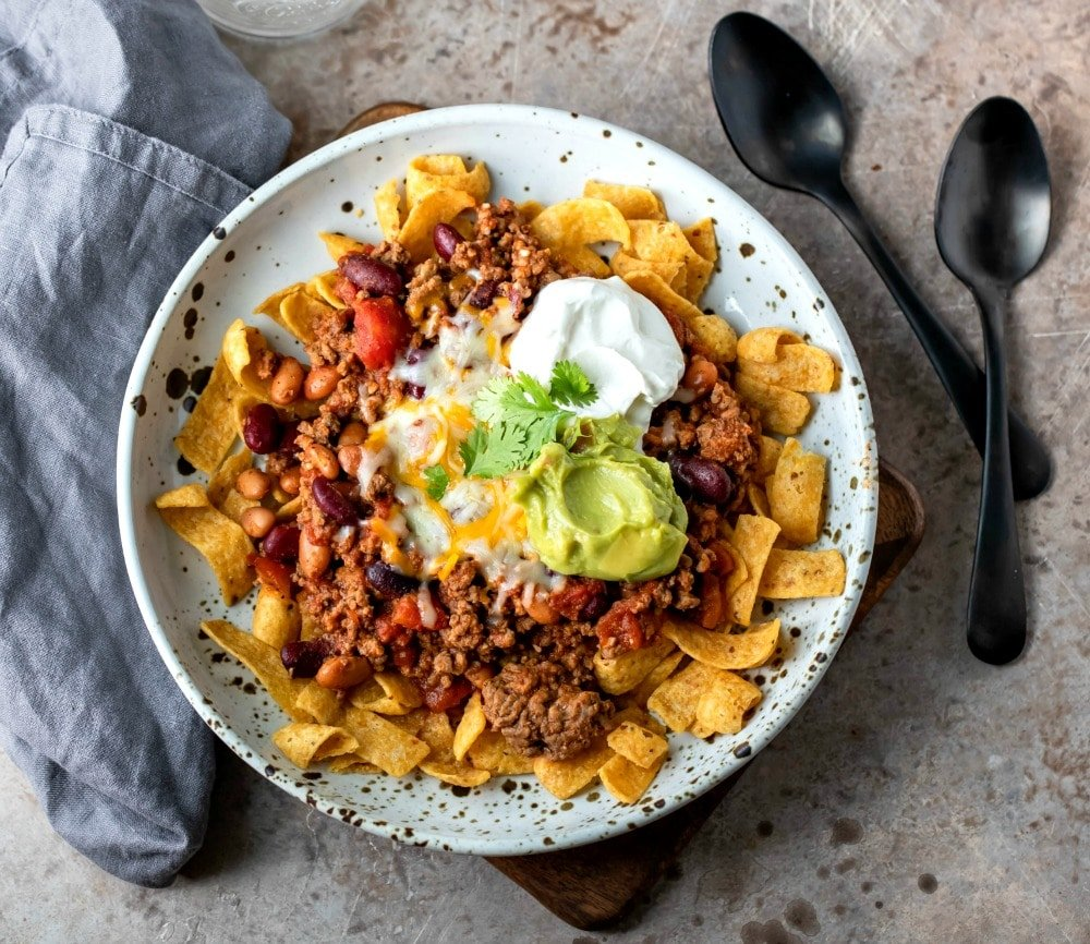 Frito chili pie on a brown speckled plate