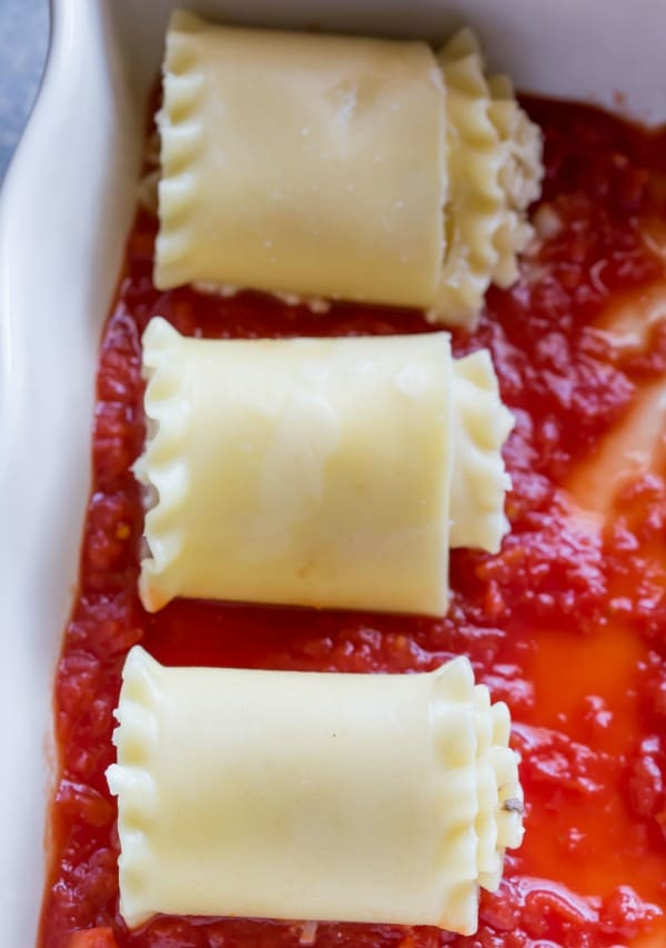 Three lasagna roll ups in a pan of sauce