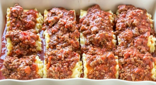 Lasagna Roll-Ups with sauce on top in a baking dish