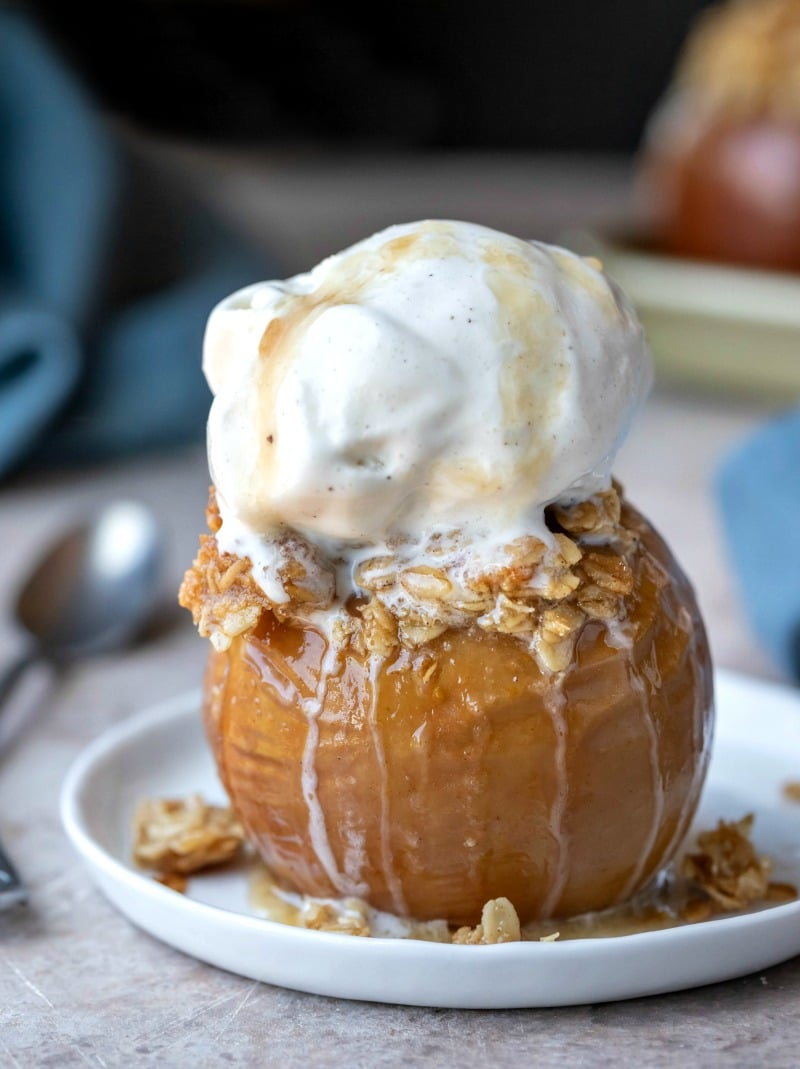 Baked apple on a white rimmed plate next to a silver spoon