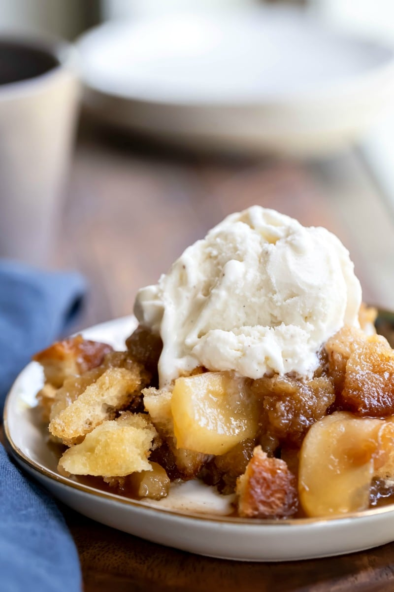 Apple Brown Betty in a white dish with a scoop of vanilla ice cream on top