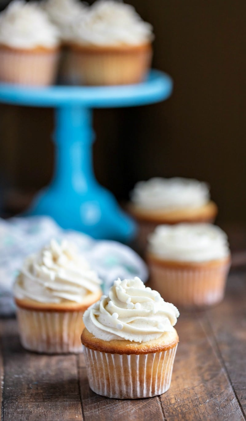 White cupcakes next to and on a blue cake stand