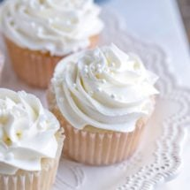 White cupcakes with white frosting on a white plate