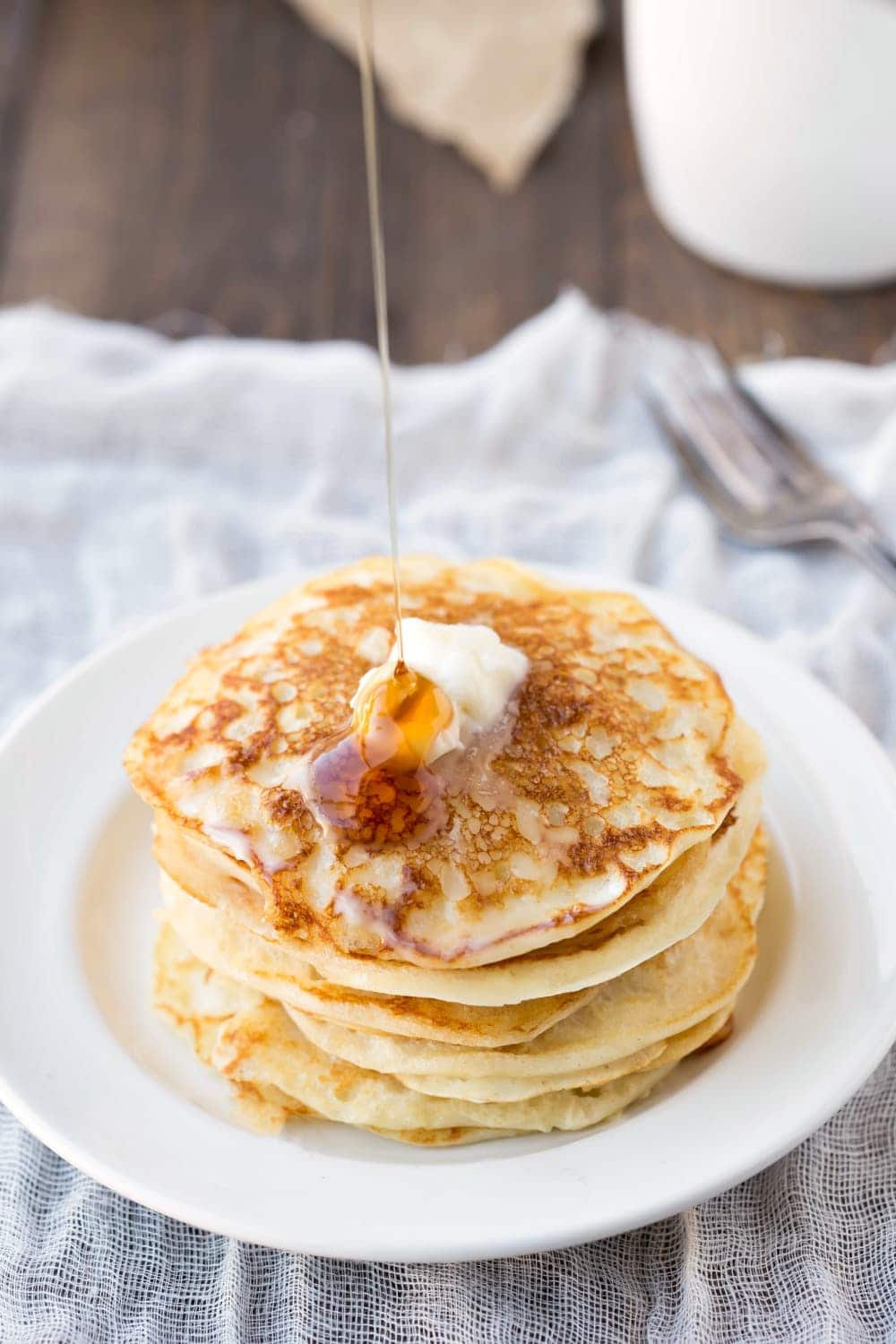 Stack of buttermilk pancakes with syrup pouring onto the top pancake