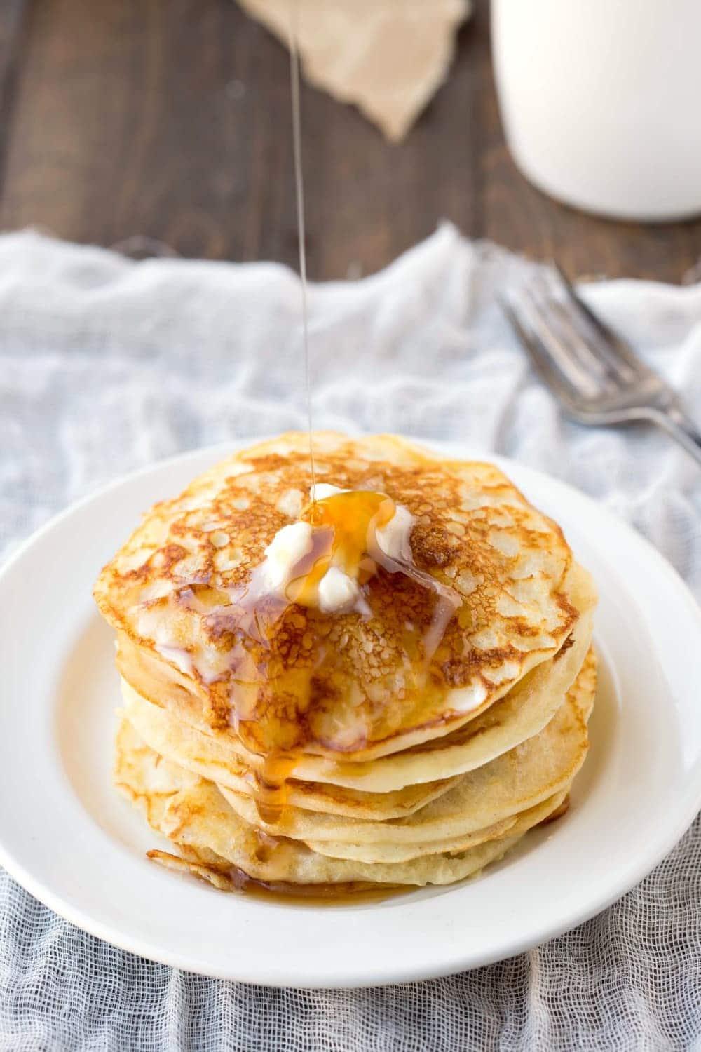 Stack of buttermilk pancakes with butter and syrup on a piece white linen cloth