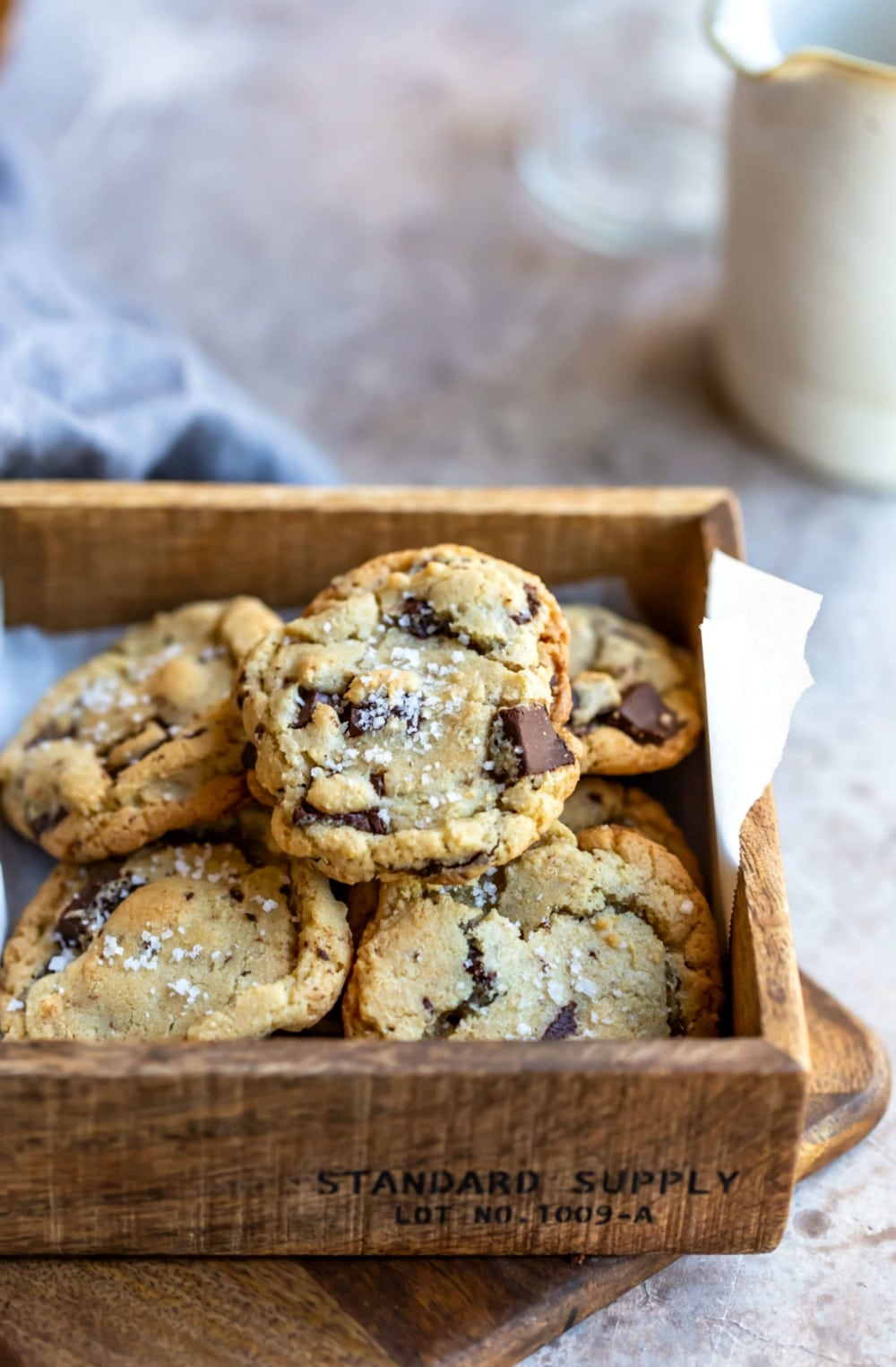 Pile of salted chocolate chip cookies in a wooden box