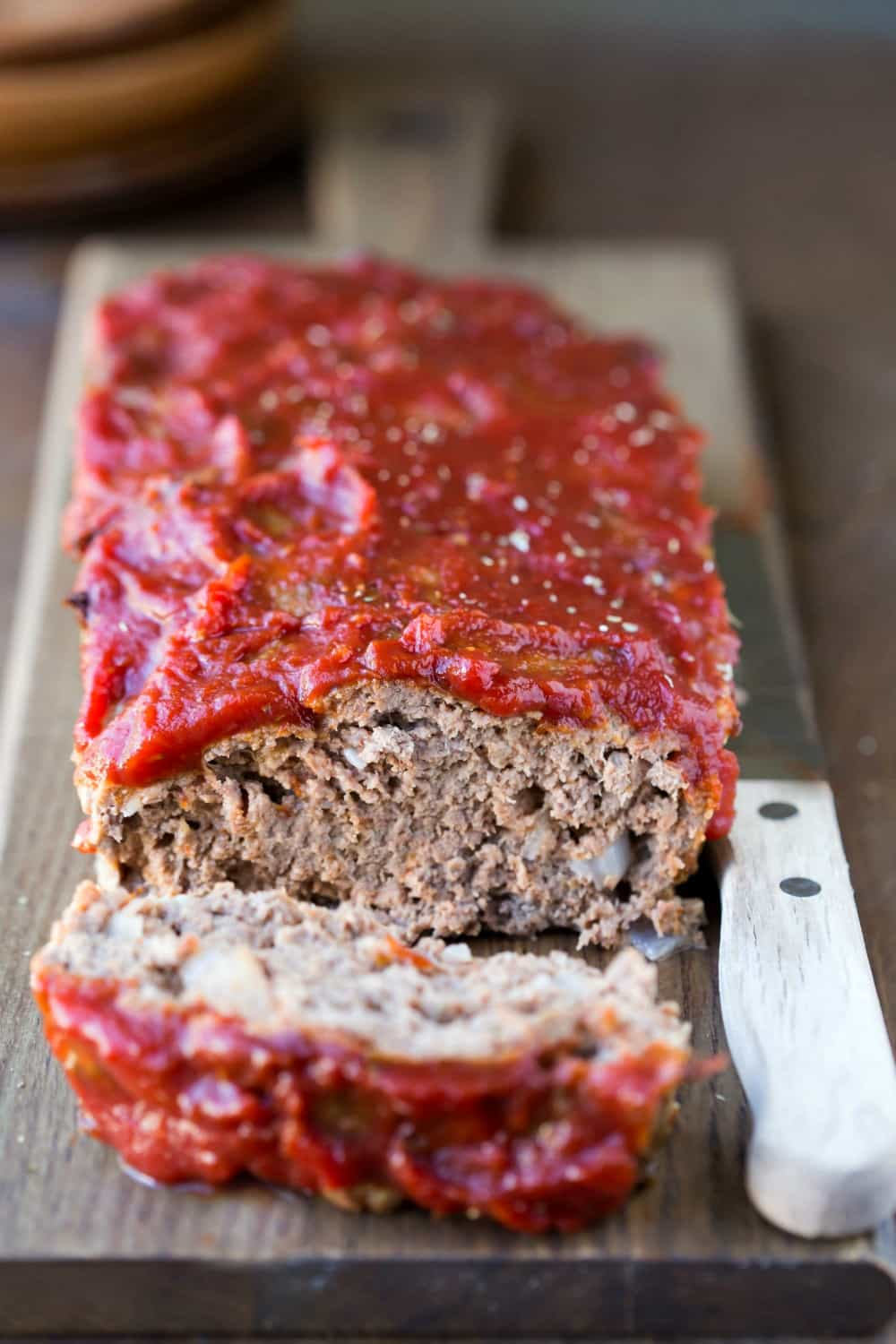 Meatloaf covered with chili sauce next to a wooden knife