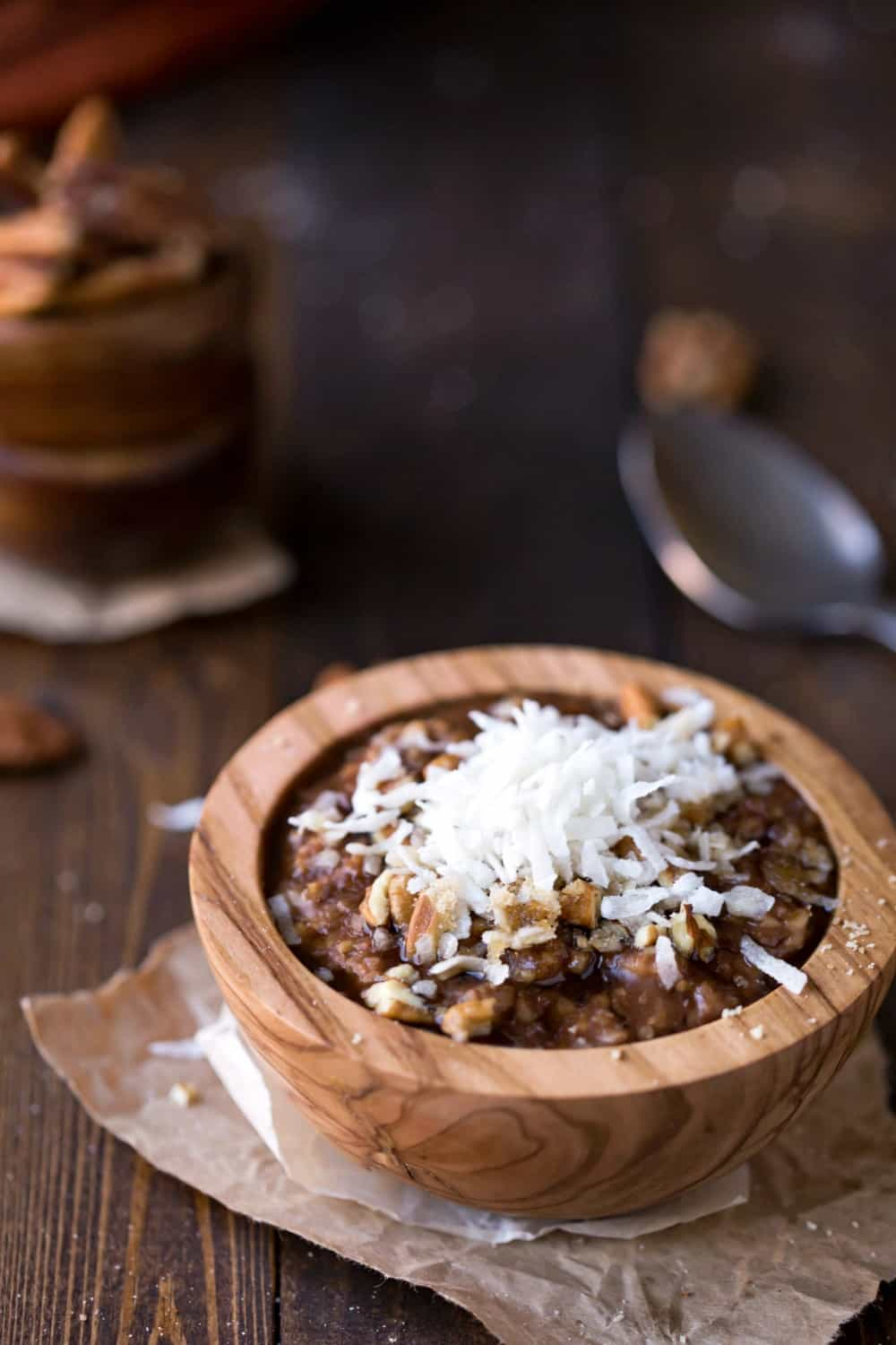 Crock Pot German Chocolate Oatmeal topped with coconut and pecans in a wooden bowl next to a spoon