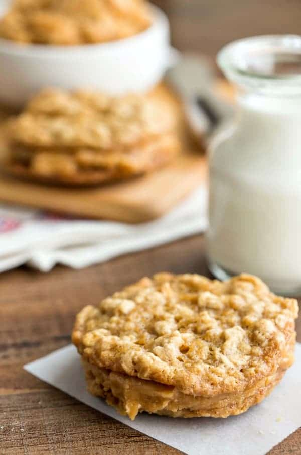 Oatmeal Cookies with Peanut Butter Filling on a piece of parchment paper next to a glass of milk
