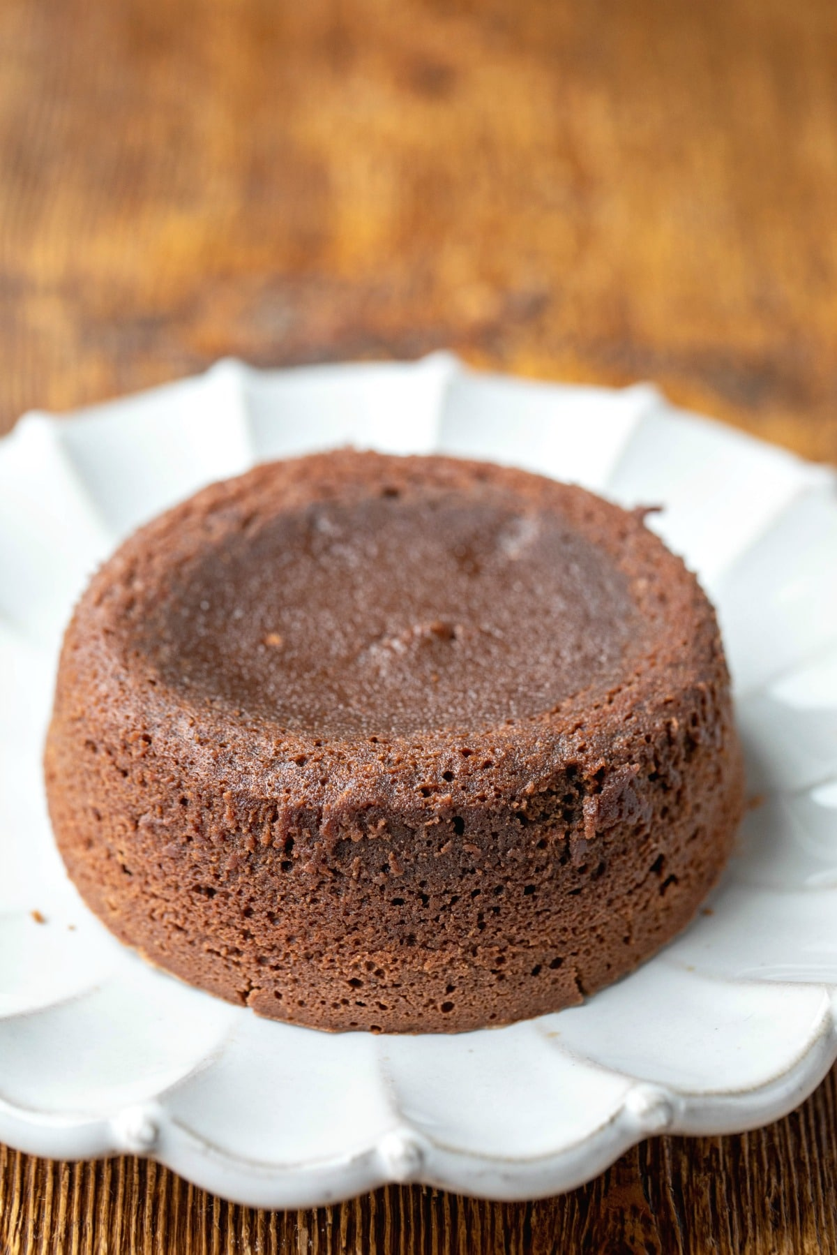 Baked molten chocolate cake on a white scalloped plate