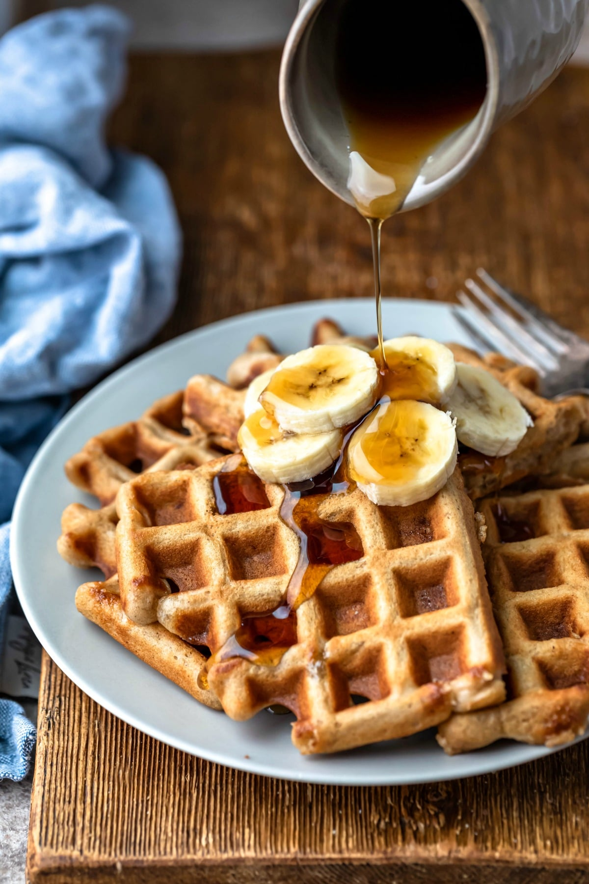 Plate of banana bread waffles next to a blue linen napkin
