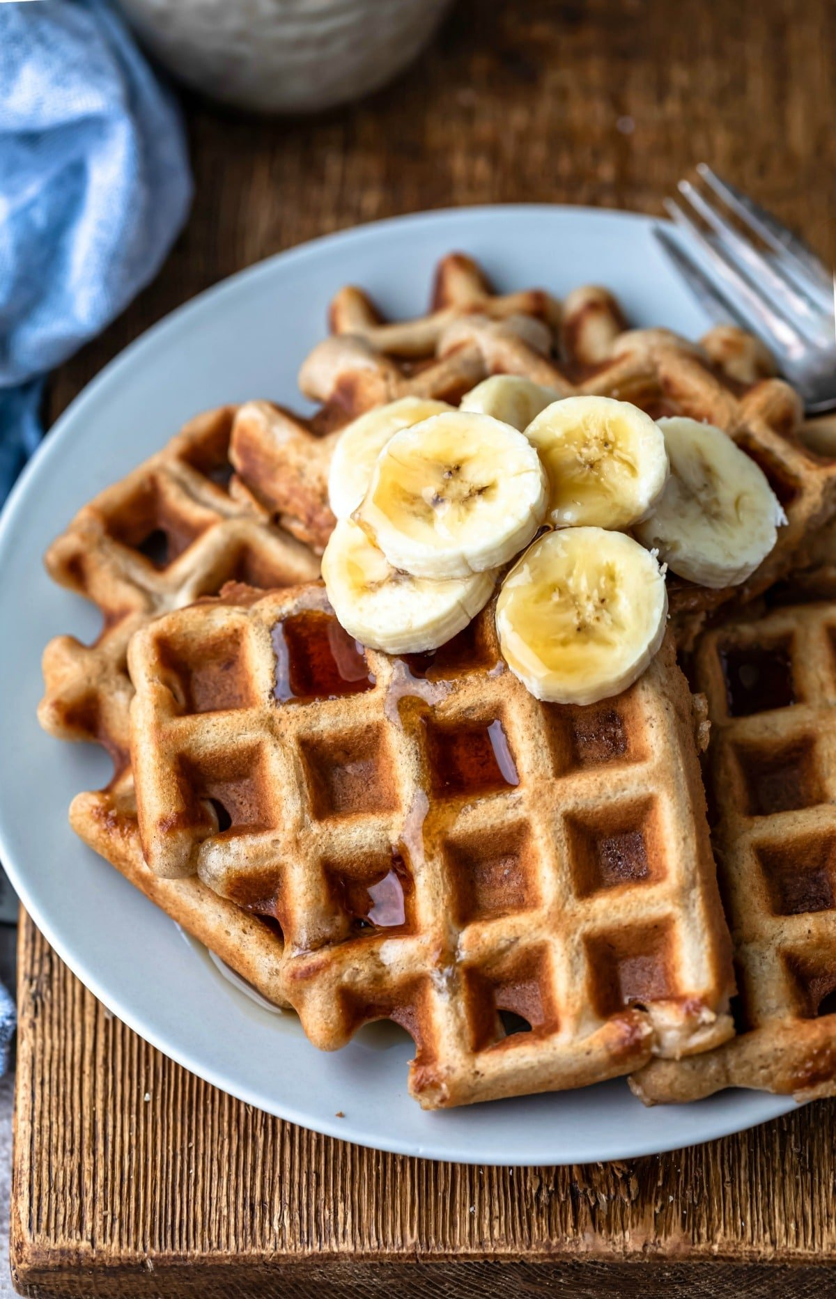 Plate of banana bread waffles topped with sliced bananas