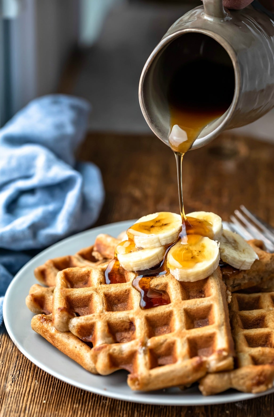 Maple syrup pouring onto banana bread waffles