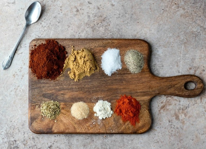Spices on a wooden cutting board for taco seasoning