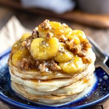 Stack of vanilla pancakes with caramelized bananas on a blue plate