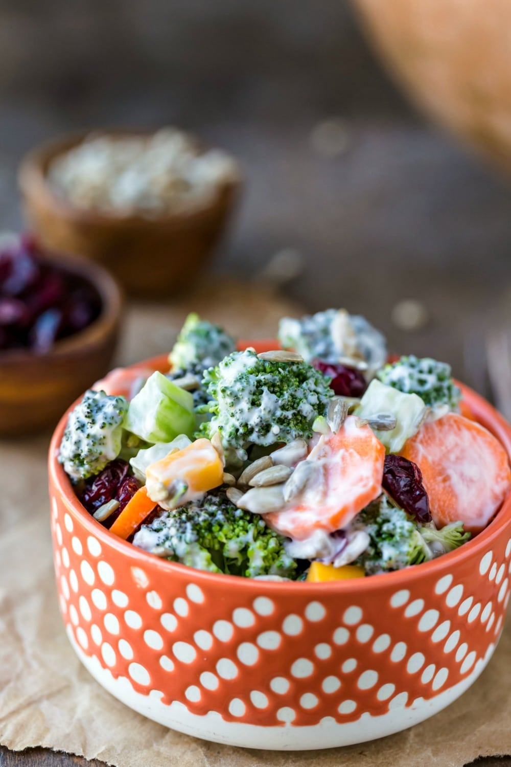 Broccoli salad in an orange and tan dish on a piece of brown paper