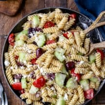 Dish of Greek pasta salad with wooden serving spoons in it