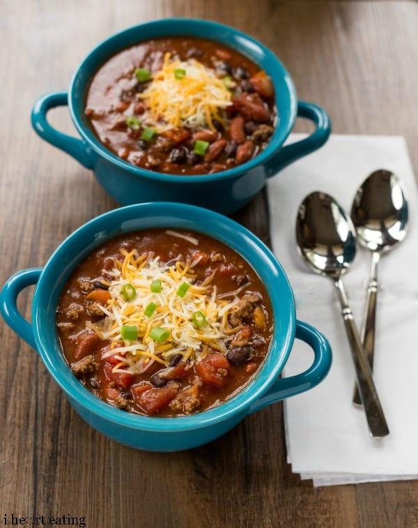 Two bowls of Barbecue Chili next to silver spoons