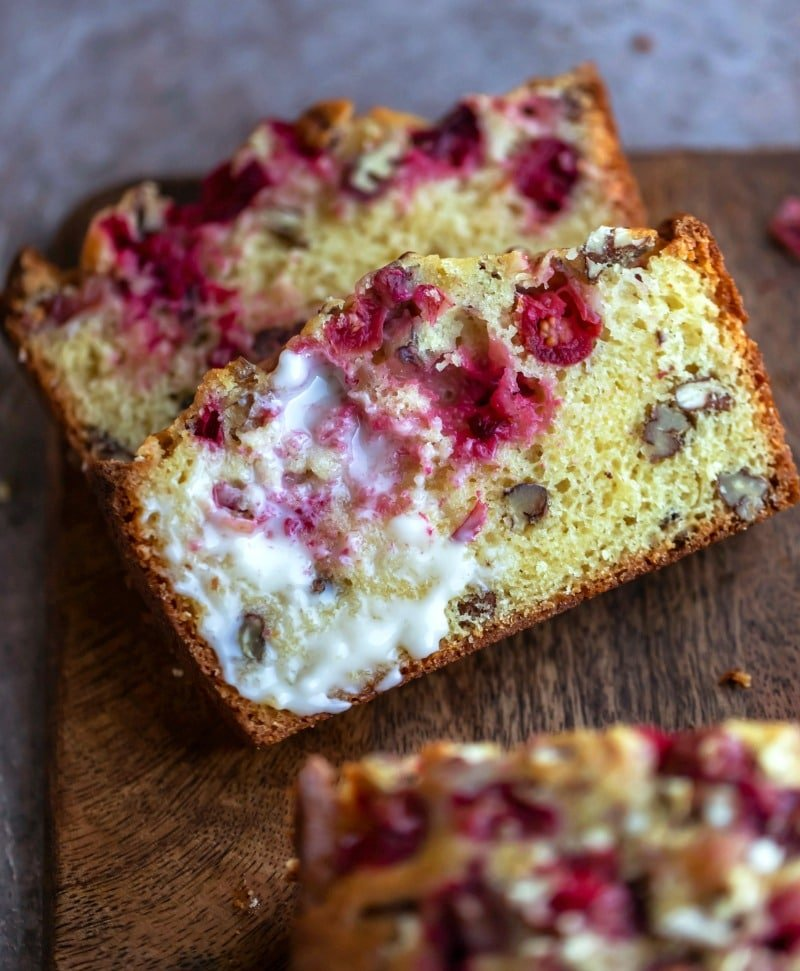Two slices of cranberry nut bread on a wooden cutting board