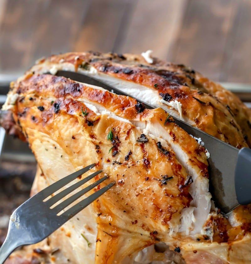 Black knife slicing lemon herb turkey breast