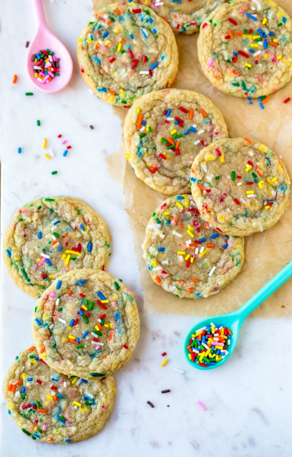 Homemade funfetti cookies next to spoons with sprinkles