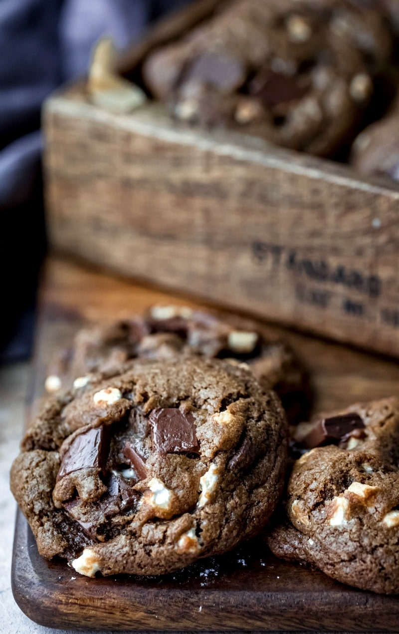 Three hot chocolate cookies on a wooden cutting board