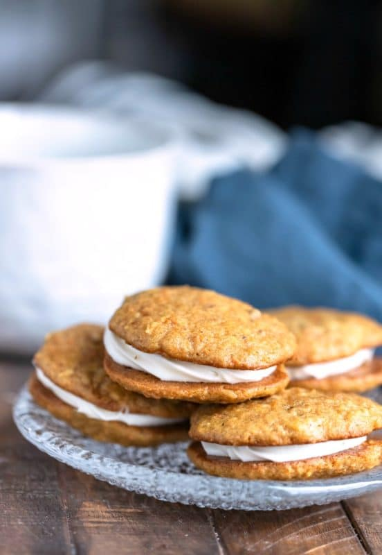 Four carrot cake sandwich cookies on a glass plate