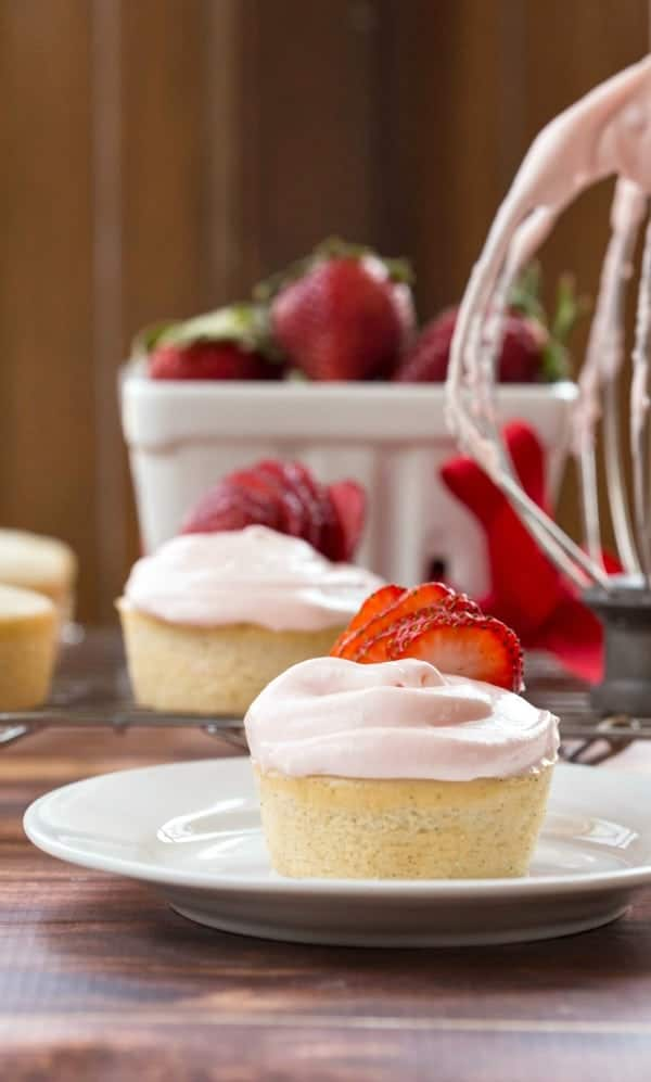Strawberry Cream Cheese Frosting on a white cupcake topped with strawberry slices