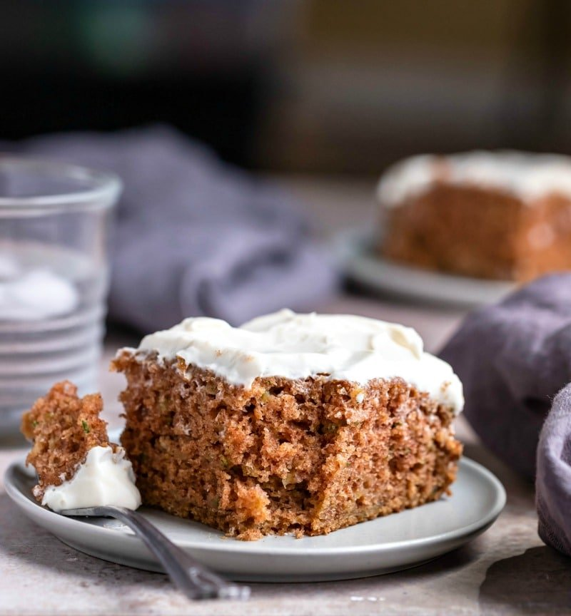 Slice of zucchini cake with a fork and bite of cake next to it