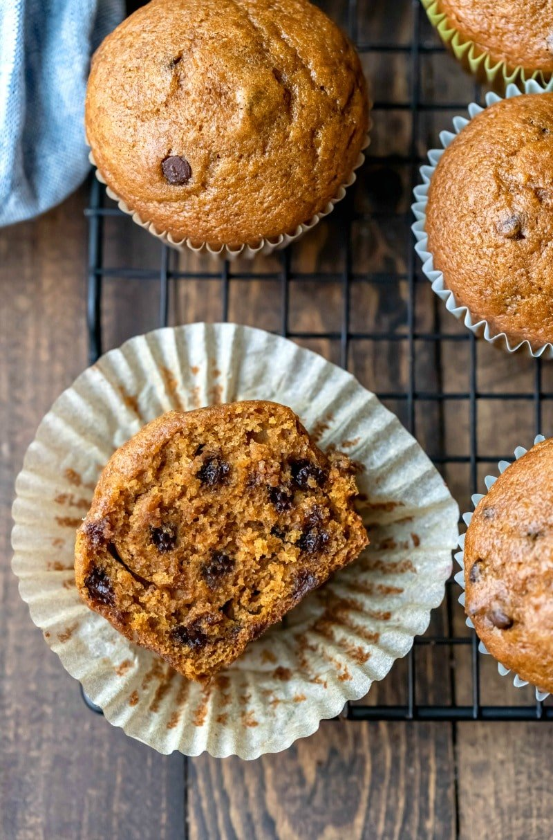Half of a pumpkin chocolate chip muffin on a wire cooling rack
