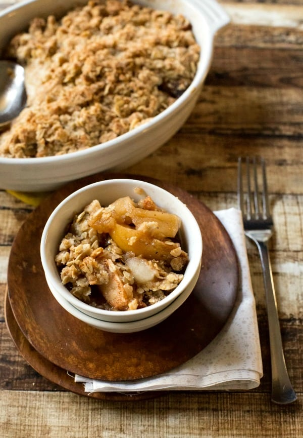 Apple Crisp In a white dish sitting on a wooden plate