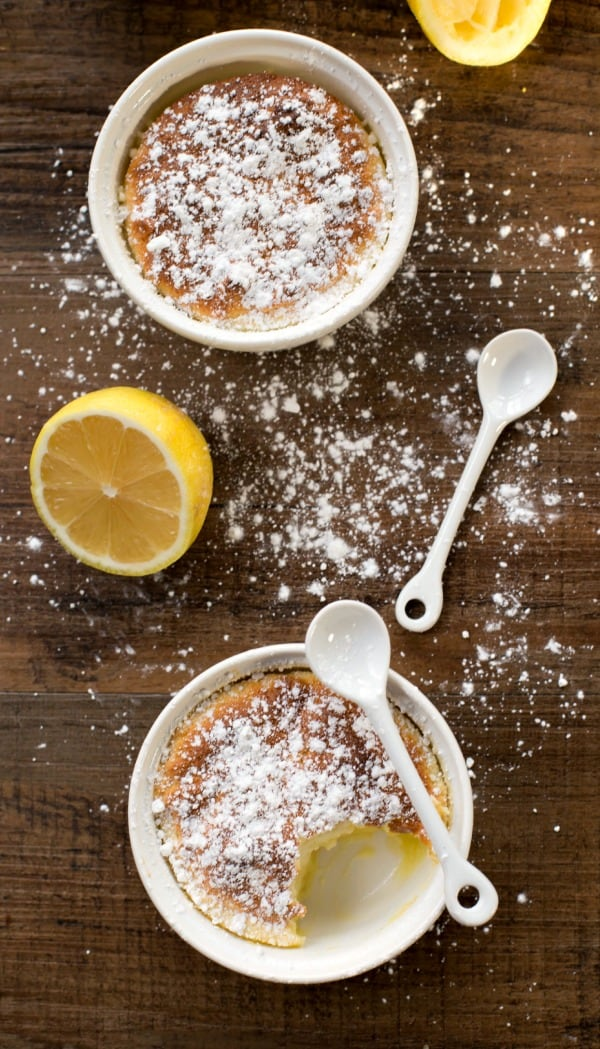 Lemon Pudding Cakes dusted with powdered sugar next to white spoons