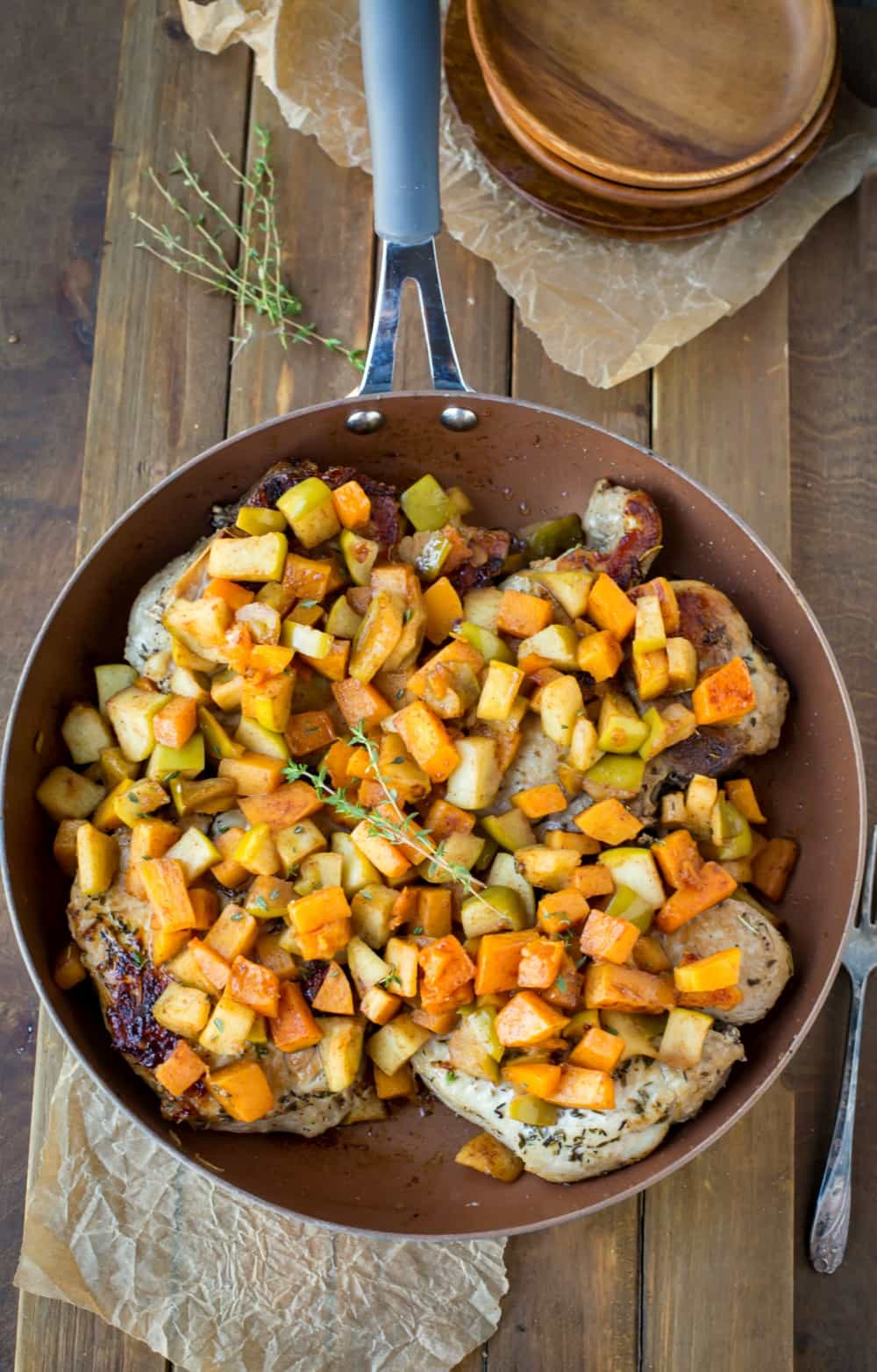 Pork Chops with Cinnamon Apples and Butternut Squash in a copper skillet topped with thyme