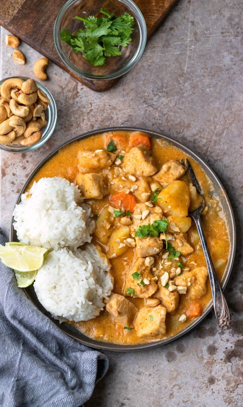 Chicken massaman curry on a plate with 2 scoops of rice