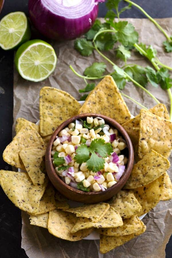 Fresh Corn Salsa in a wooden bowl surrounded by chips