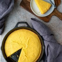 Cast iron skillet of cornbread with one slice missing